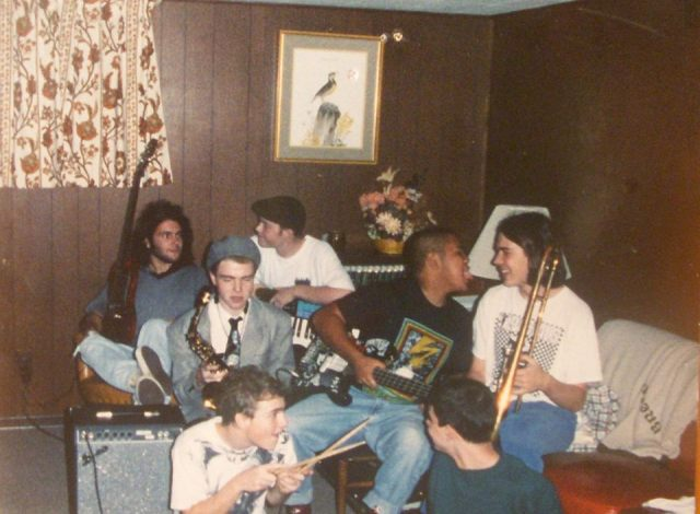 a photo of a very early line up of The Preschoolers circa 1993 at their first rehearsal in Towson, Md. at Eddie Macintosh's mom's house:(top left to right) Diego Ramos, Eddie Macintosh, Bob Phair, Lee Versoza, Dave Willemain; (bottom left to right) Joe Mysko, Sam Frazier, (photo taken with an automatic camera by Diego Ramos)